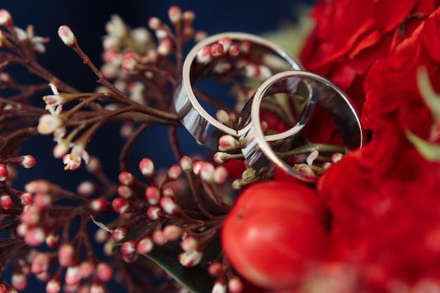 Anéis de casamento de ouro branco clássico no buquê vermelho Foto gratuita