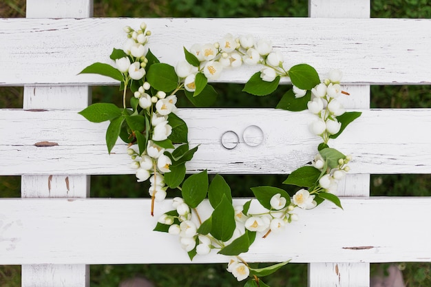 Anéis de casamento de ouro com diamantes encontram-se dentro da flor de jasmim no bouquet de noiva Foto Premium