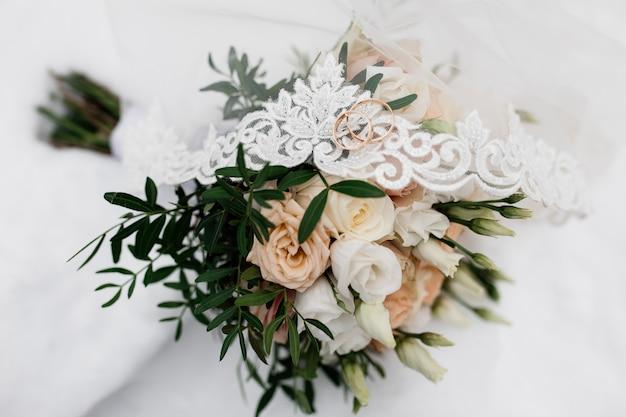 Anéis de casamento estão no véu de noiva e flores Foto gratuita