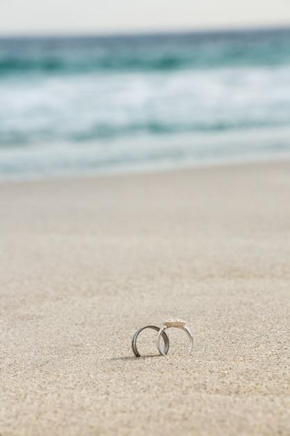 Anéis de casamento na areia Foto gratuita