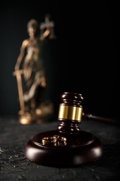 Anéis de casamento na placa de madeira e martelo do juiz Foto Premium