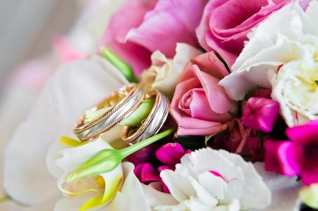 Anéis de casamento no buquê da noiva de rosas e coalas. Foto Premium