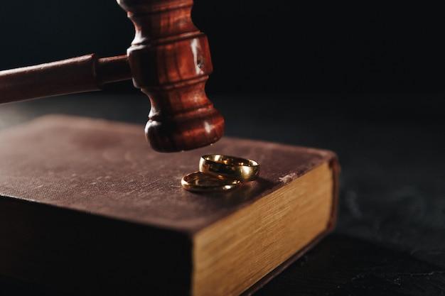 Anéis de casamento no livro e martelo do juiz Foto Premium