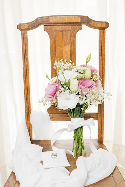 Anéis de casamento no travesseiro branco com cachecol e buquê sobre a cadeira de madeira perto da cortina Foto gratuita