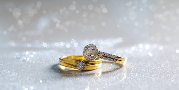 Anéis de diamante dos pares do casamento colocados na terra branca. há pó de diamante. Foto Premium