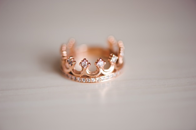 Anel de coroa com pedras preciosas em cima da mesa Foto Premium