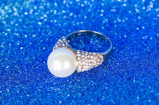 Anel de jóias contra o fundo azul Foto Premium