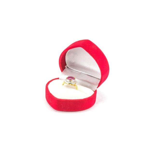 Anel de pedra seixo rosa closeup em caixa de forma de coração vermelho isolada no branco Foto Premium