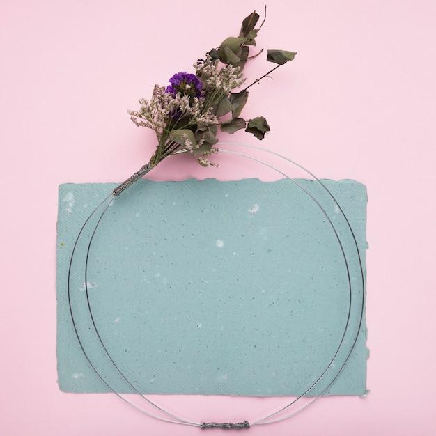 Anel metálico com buquê de flores em papel sobre o pano de fundo-de-rosa Foto gratuita