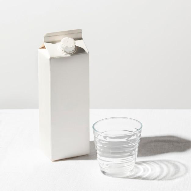 Ângulo alto da caixa de leite com o copo vazio Foto gratuita