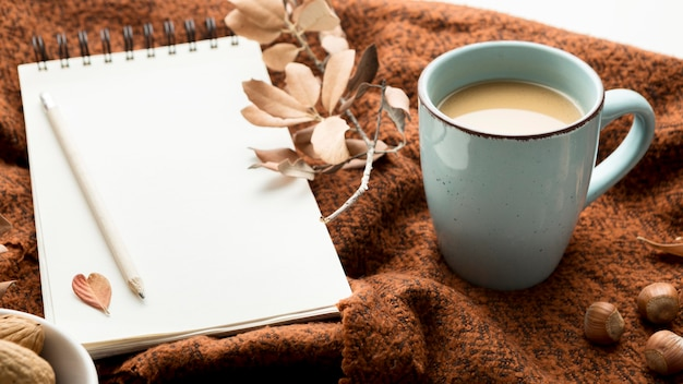 Ângulo alto da caneca de café com folhas de outono e caderno Foto gratuita