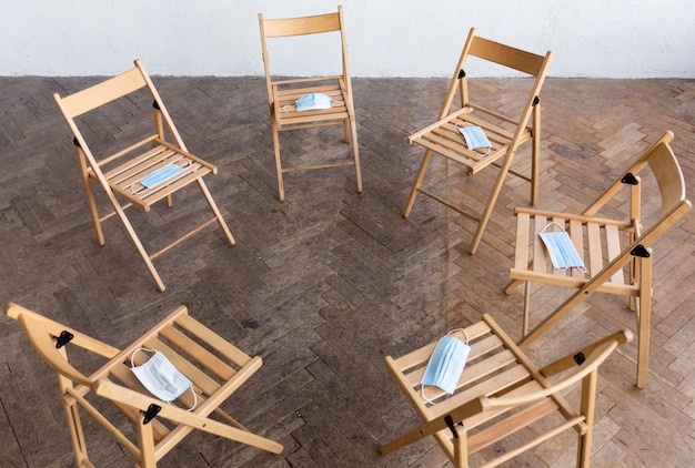Ângulo alto de cadeiras vazias com máscaras médicas preparadas para sessão de terapia de grupo Foto gratuita