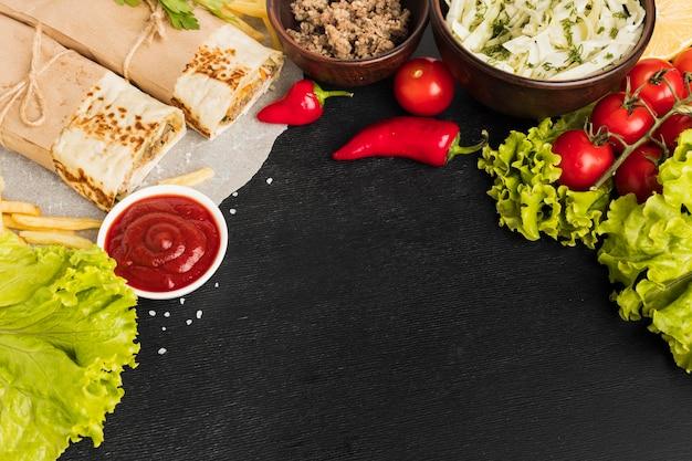 Ângulo alto de delicioso kebab com tomate e salada Foto gratuita