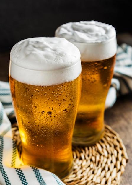 Ângulo alto de dois copos de cerveja com pano Foto Premium