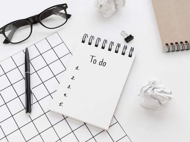 Ângulo alto de lista de tarefas no bloco de notas com óculos e caneta Foto gratuita