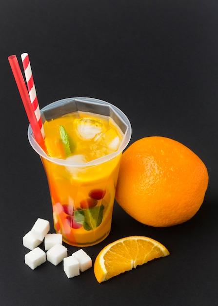 Ângulo alto de suco de fruta em copo com canudos Foto gratuita