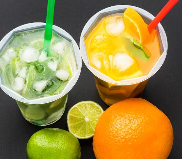 Ângulo alto de suco de frutas em copos com canudos Foto gratuita