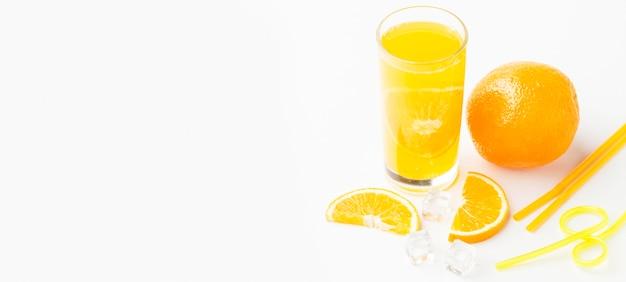 Ângulo alto de suco de laranja em vidro com espaço para casca e cópia Foto gratuita