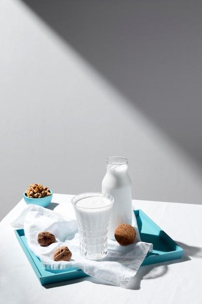 Ângulo alto do copo de leite e garrafa com nozes e espaço de cópia Foto gratuita