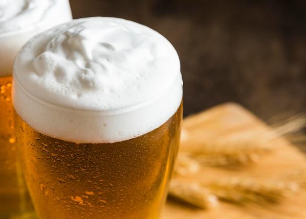 Ângulo alto dos copos de cerveja com espuma Foto gratuita