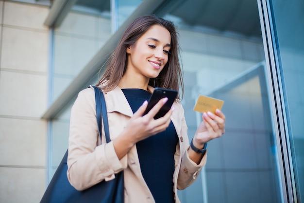 Ângulo baixo da garota satisfeito em pé no saguão do aeroporto. ele está usando cartão de crédito gold e celular para pagar Foto Premium