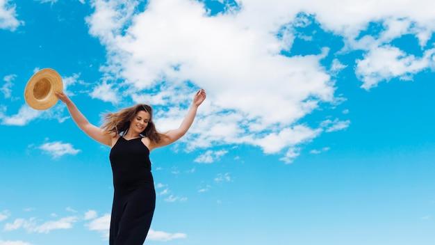 Ângulo baixo de mulher, desfrutando de um belo dia com céu e nuvens Foto gratuita