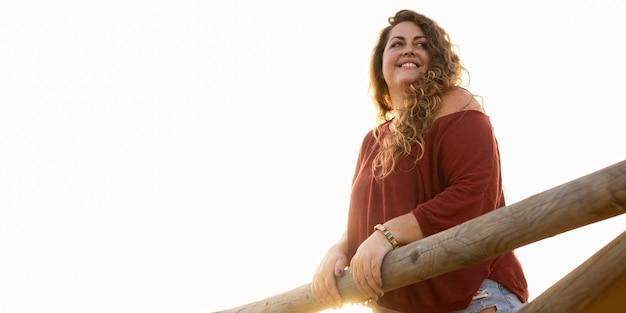 Ângulo baixo de mulher posando ao ar livre Foto gratuita