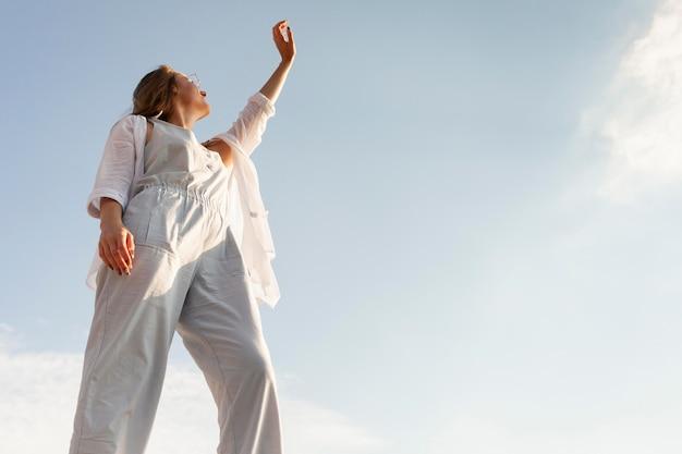 Ângulo baixo de mulher posando ao sol com céu claro Foto gratuita