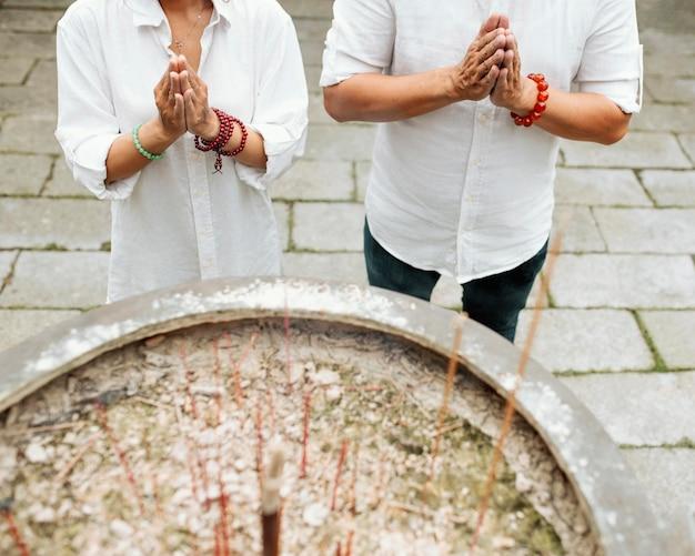 Ângulo elevado de mulher e homem orando no templo com incenso queimando Foto gratuita