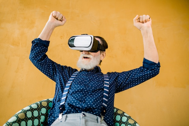 Animado alegre barbudo homem elegante camisa azul escura e suspensórios, usando óculos 3d vr e assistindo filme ou jogo de futebol com sorriso e punhos cerrados Foto Premium
