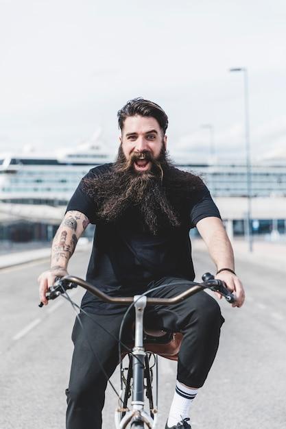 Animado barbudo jovem desfrutando de andar de bicicleta Foto gratuita
