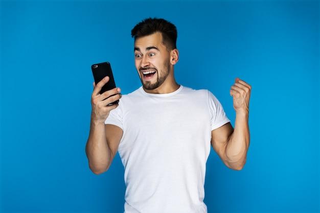 Animado cara europeu está assistindo no celular Foto gratuita