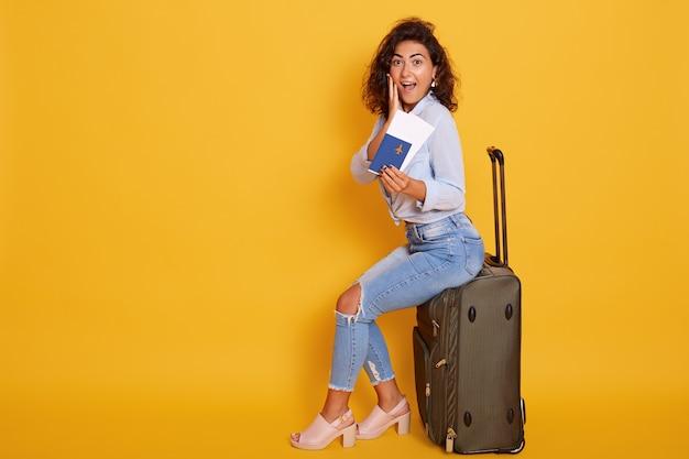 Animado e feliz alegre jovem turista feminina sentado em sua mala grande Foto gratuita