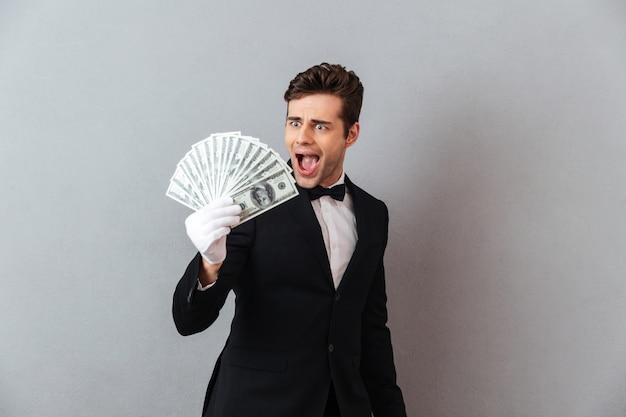 Animado gritando jovem garçom segurando o dinheiro. Foto gratuita