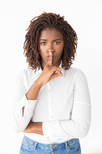 Animado jovem silenciosa fazendo gesto de silêncio Foto gratuita