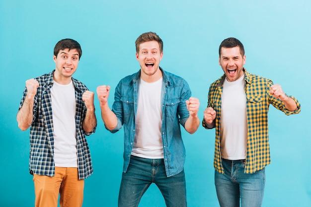 Animado jovens amigos masculinos cerrando o punho contra o fundo azul Foto gratuita