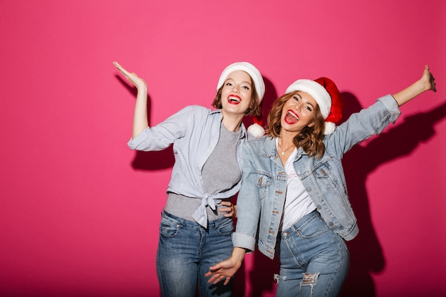 Animado, sorrindo, duas mulheres amigos usando chapéus de papai noel de natal Foto gratuita