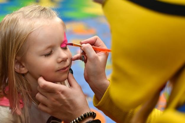Animador pinta o rosto de uma pintura de menina em um feriado Foto Premium