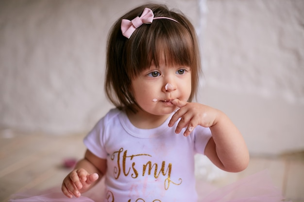 Aniversariante bebê encantador no vestido rosa senta-se na cadeira Foto gratuita