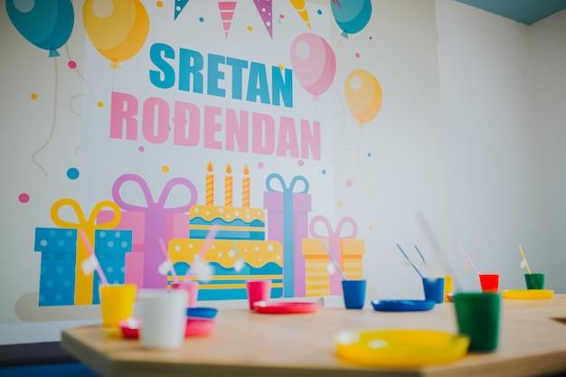 Aniversário em uma creche com talheres coloridos nas pequenas mesas de madeira Foto gratuita