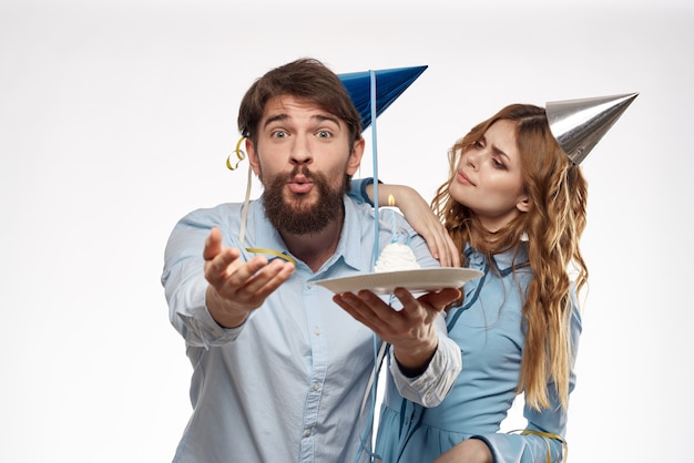 Aniversário homem e mulher com um bolinho e uma vela com um chapéu de festa Foto Premium