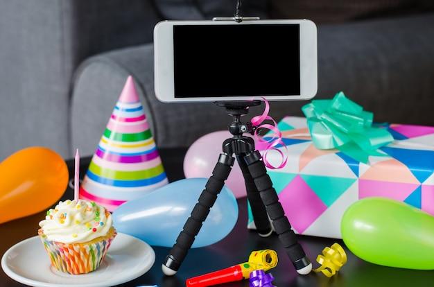 Aniversário online. smartphone, bolo de aniversário, presentes e acessórios de férias. Foto Premium