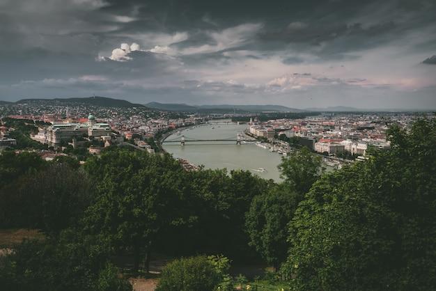 Anjo alto tiro de uma paisagem urbana com um rio no meio e árvores ao redor da vista Foto gratuita