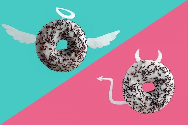 Anjo e demônio donuts em um fundo azul e rosa Foto Premium