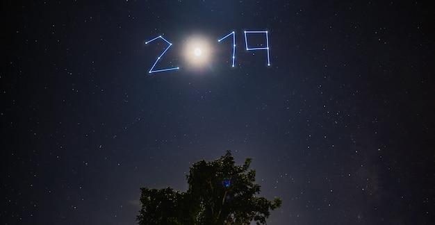 Ano novo, 2019, estrela, e, lua, brilho, sobre, árvore, em, noite azul Foto Premium