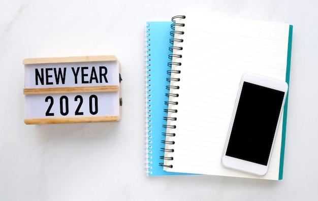 Ano novo 2020 em caixa de madeira, papel de caderno em branco e telefone com tela em branco sobre fundo de mesa de mármore branco Foto Premium