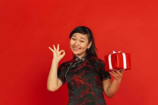 Ano novo chinês. retrato de jovem asiático isolado sobre fundo vermelho. modelo feminino com roupas tradicionais parece feliz com a caixa de presente. celebração, feriado, emoções. mostrando simpático, sorrindo. Foto gratuita