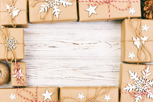 Ano novo e composição de quadro de natal. caixas de presente de natal embrulhado artesanal com decoração em branco com copyspace vazio para o seu texto. acima da vista, plana leigos. toned Foto Premium