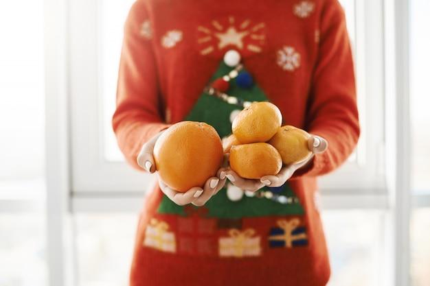 Ano novo e o conceito de inverno. foto recortada de fêmea na camisola de natal engraçado segurando laranja e tangerinas, oferecendo ao amigo, em pé perto da janela. menina ficou doente e namorado trouxe vitamina c Foto gratuita