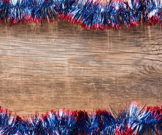 Ano novo, fundo de natal com espaço de cópia. tábuas de madeira velhas emolduradas por ouropel azul Foto Premium